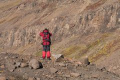 Armed expedition leader secures the terrain in Greenland. Armed expedition leader secures the terrain in east Greenland to protect a group of tourists Stock Images