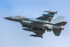 Armed F16 fighter jet. F16 fighter jet armed with rockets and external fuel tanks stock photo