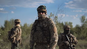 Armed force in nature. The commander in a military uniform and with weapon stand against the background of soldiers and looks in the camera stock video