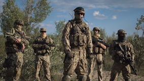 Armed force in nature. Group of soldiers in a camouflage and the hidden persons with weapon pose and look in the camera stock video