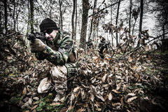 Armed forces. Special forces patrol in woods Royalty Free Stock Photo