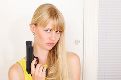 Armed girl at door Stock Images