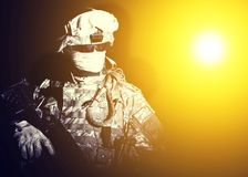 Special forces soldier in projector dazzling light. Armed infantry with hidden face standing in blinding light of projector or searchlight during combat, counter Stock Photo
