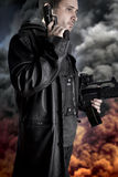 Armed man on background with explosion Stock Images