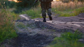 An armed man in camouflage uniforms walks along a dirt road at sunset. Back view stock video footage