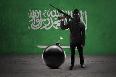 Armed man with flag of Saudi Arabia. Concept of terrorism. A male terrorist standing in front of Saudi Arabian flag while holding rifle with bomb Stock Image