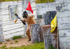 Armed man setting up victory flag in paintball mission Stock Images