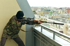 Armed man with weapon. Aiming from abandoned building Stock Photo