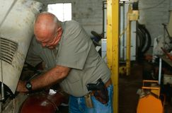 An armed man working in a garage, South Africa Royalty Free Stock Photos