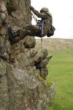 Armed military alpinist climbing Stock Photography