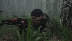 Armed military man in forest. Unrecognizable soldier lying in forest and aiming with assault rifle stock video