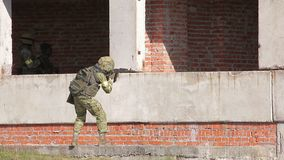 Armed soldier with automatic rifle aiming. Armed modern soldier with automatic rifle preparing to shoot target. Heavy combat ammunition and bulletproof stock footage