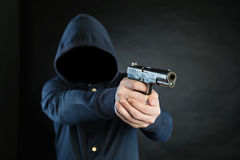 Armed person in a hoodie is pointing a handgun at the target. Stock Image
