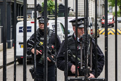 Armed Police guard the Gates into Downing Street in Westminster, London. Royalty Free Stock Images