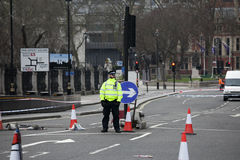 An armed police officer stands guard near Westminster Bridge and Stock Image