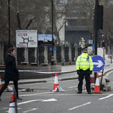 An armed police officer stands guard near Westminster Bridge and Royalty Free Stock Photo