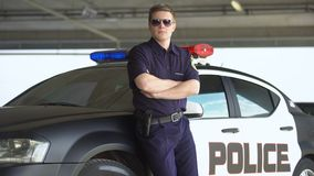 Armed policeman in sunglasses standing near patrol car, dangerous profession. Stock footage stock video footage