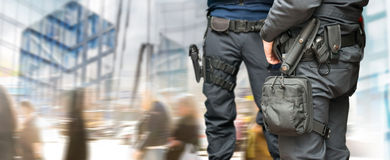 Armed policemen. On guard in busy street with modern glass buildings and people walking royalty free stock photos