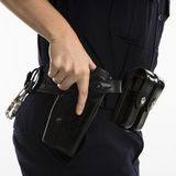 Armed policewoman. Close up side view of mid adult female Caucasian law enforcement officer hand on gun in holster Royalty Free Stock Image