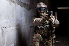Armed ranger in camouflage aiming his gun in the dark room. Armed ranger in camouflage,mask and helmet aiming his gun in the dark room royalty free stock photos