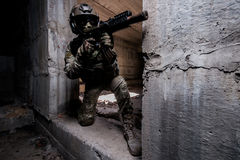 Armed ranger in in mask and helmet hiding in a building. Armed ranger in in mask,helmet and camouflage hiding in a building during the military operation stock photos