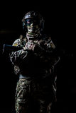Armed ranger standing and looking at the camera. Ranger in camouflage,mask and helmet standing with rifle and looking at camera on black background stock images