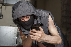 Armed robber with a gun in the attic Royalty Free Stock Image
