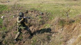 Armed soldier with automatic rifle. Armed modern soldier with automatic rifle preparing to shoot target. Heavy combat ammunition and bulletproof protective stock video