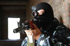 Armed soldier in black mask targeting with a gun Stock Image