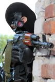 Armed soldier in black mask targeting with a gun Stock Photos