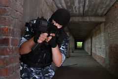 Armed soldier in black mask targeting with a gun Stock Photo
