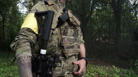 An armed soldier with a rifle and military uniform standing in the woods and smokes. A group of armed men in camouflage stock video footage