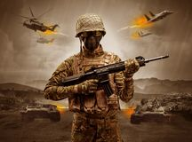 Armed soldier standing in the middle of a war. Armed soldier with sniper in the middle of a war royalty free stock photos