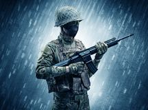 Soldier standing in rainy weather stock images
