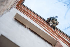 Armed soldiers on the edge of the roof. Soldier with a gun on the edge of the roof coming down on a rope royalty free stock photos