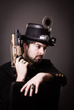 Armed steampunk man. Armed man in steampunk outfit holding a gun in his hand and a hat on his head royalty free stock photography