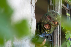 Armed terrorist looking out of window Stock Images