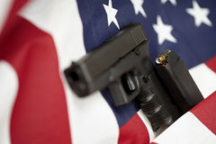 Armed United States of America gun and USA flag Royalty Free Stock Photos