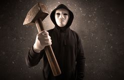 Armed villain in an empty dark room. Masked armed villain in empty dark room with gun ax chainsaw mallet wrench stock image