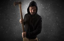 Armed villain in an empty dark room. Masked armed villain in empty dark room with gun ax chainsaw mallet wrenchn stock photo