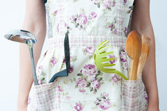 Armed woman cook. The multifunctional woman cook with lots of kitchen tools Royalty Free Stock Photography