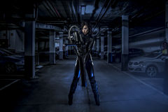Armed woman in a garage, future concept, black latex with neon l Stock Photos