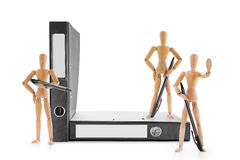 Armed wooden mannequins guarding office folders Stock Images