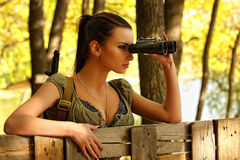 Armed young beautiful girl looking through binoculars Stock Photos