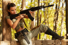 Armed young beautiful shoots a machine gun sitting on the fence. Royalty Free Stock Photo
