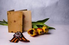 Armeebücher Bestellungs-, St- Georgeband und farbige Tulpen Stockfotos