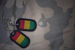 Armeefreier raum, Erkennungsmarke mit Flagge der Guine auf dem kakifarbigen Beschaffenheitshintergrund lizenzfreie stockbilder