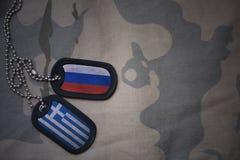 Armeefreier raum, Erkennungsmarke mit Flagge von Russland und Griechenland auf dem kakifarbigen Beschaffenheitshintergrund stockfotografie