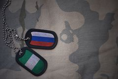 Armeefreier raum, Erkennungsmarke mit Flagge von Russland und Nigeria auf dem kakifarbigen Beschaffenheitshintergrund Stockbild