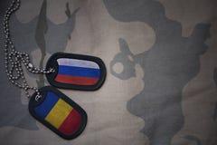Armeefreier raum, Erkennungsmarke mit Flagge von Russland und Rumänien auf dem kakifarbigen Beschaffenheitshintergrund Stockbild